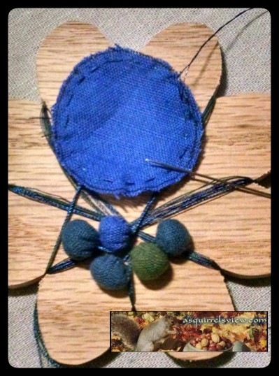 Finished blue buttons wrapped around a thread  winder with one button started